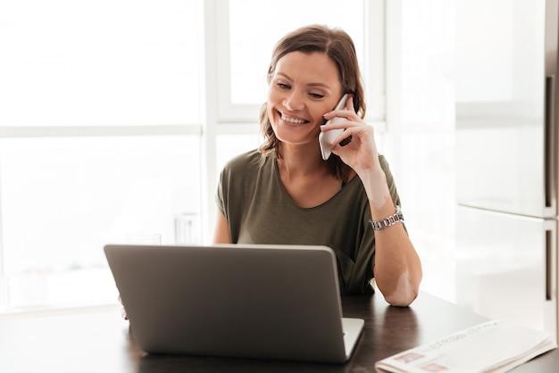 Glückliche lässige frau, die durch smartphone spricht, während sie nahe dem tisch mit laptop-computer sitzt