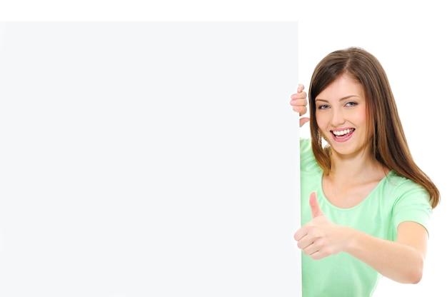 Glückliche lässige frau mit einem leeren banner, das daumen hoch zeigt