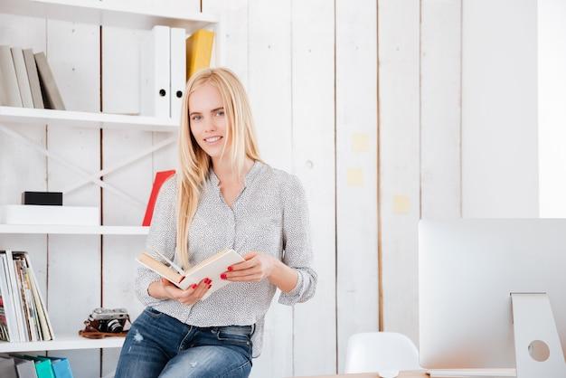 Glückliche lässige geschäftsfrau, die ein buch hält und im büro auf dem schreibtisch sitzt