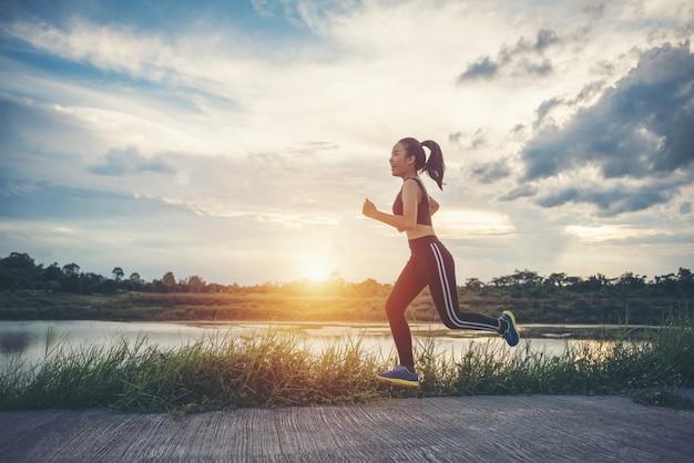 Glückliche läuferfrau läuft in der rüttelnden übung des parks.