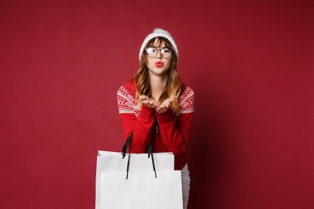 Glückliche langhaarige frau in der winterkleidung mit einkaufstaschen