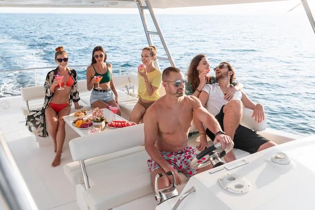 Glückliche leute, die eine schicke party auf einem luxusboot haben. gruppe von freunden, die party auf einer yacht machen.