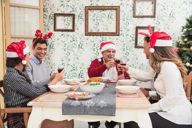 Glückliche leute, die gläser am weihnachtstisch klopfen