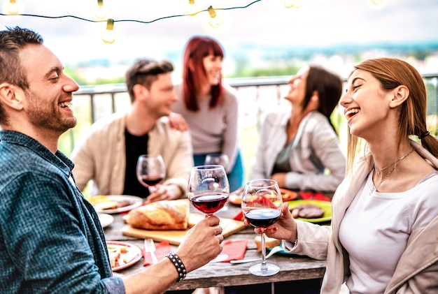 Glückliche leute, die spaß haben, wein auf der terrasse bei privater dinnerparty zu trinken