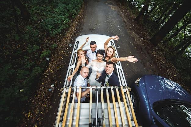 Glückliche leute im auto feiern hochzeit