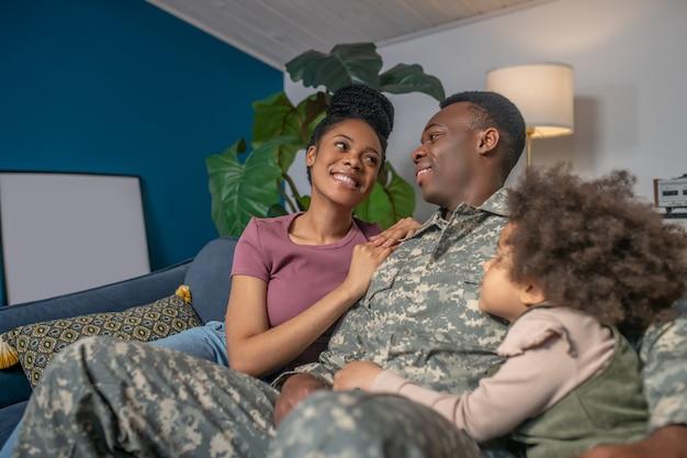 Glückliche leute. junger erwachsener dunkelhäutiger mann in militäruniform und lächelnde frau, die sich ansieht und kleine tochter, die auf sofa sitzt