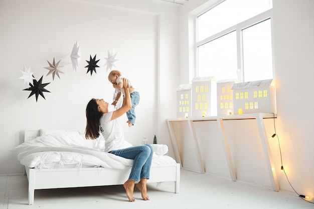 Glückliche liebende familie mutter spielt mit ihren kindern im schlafzimmer