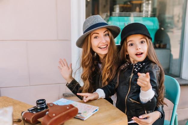 Glückliche liebende familie. mutter und ihre tochter sitzen in einem stadtcafé und schauen überrascht in die kamera und das mädchen, das den weg zeigt. auf dem tisch liegen eine karte und kameras. wahre gefühle, gute laune ..