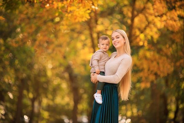 Glückliche liebende mutter, die kleines kind in ihren armen hält