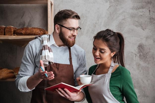 Glückliche liebende paarbäcker, die kaffee trinken, das notizbuch betrachten.