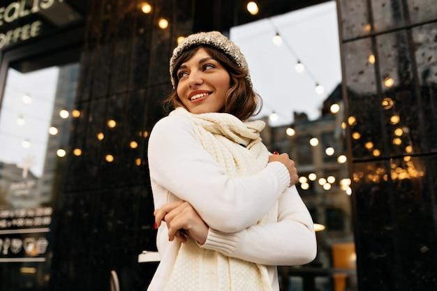 Glückliche liebenswerte frau im weißen winteroutfit, das auf der straße mit glücklichem lächeln auf hintergrund mit weihnachtslichtern hochqualitatives foto geht