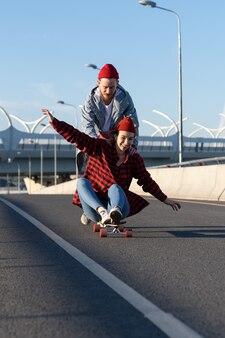 Glückliche liebespaare chillen im freien, fahren longboard, lachen und haben spaß zusammen auf der städtischen straße