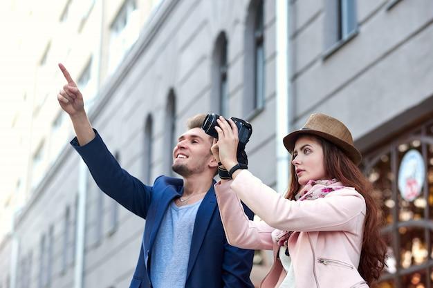 Glückliche liebespaare von den touristen, die das zeigen auf einen markstein oder einen schauplatz in der stadt nehmen