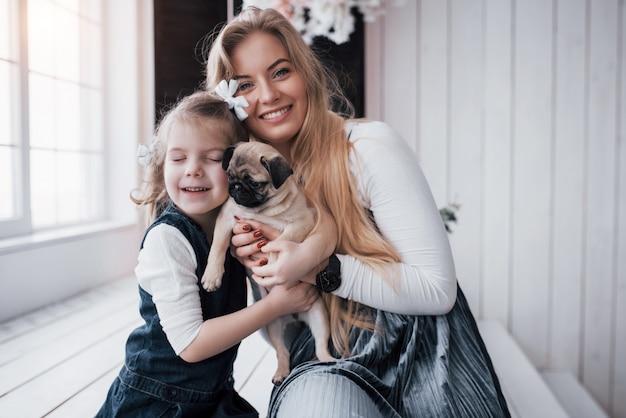 Glückliche liebevolle familie. bemuttern sie und ihr tochterkindermädchen, das entzückenden pug spielt und umarmt