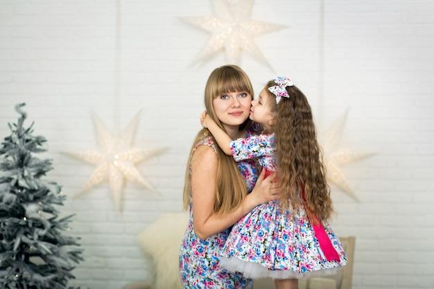 Glückliche liebevolle familie. bemuttern sie und ihr tochterkindermädchen in den gleichen spielenden und umarmenden kleidern