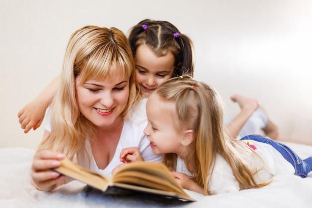Glückliche liebevolle familie. hübsche junge mutter, die ein buch zu ihrer tochter-mamma- und buch mit zwei kleinen mädchen liest