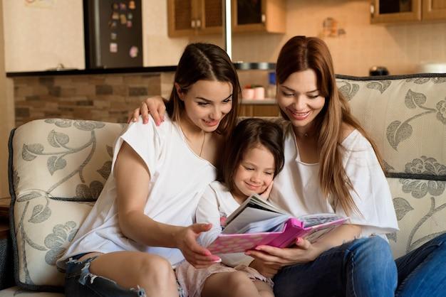 Glückliche liebevolle familie. hübsche junge mutter und ihre schwester lesen ihrer tochter ein buch vor.