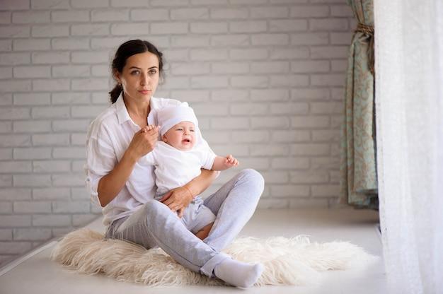 Glückliche liebevolle familie. junge mutter spielen mit ihrem baby