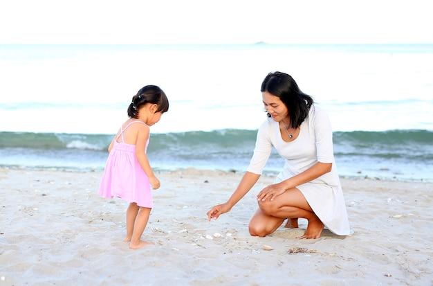 Glückliche liebevolle familie. mutter und ihr tochterkindermädchen, die sand am strand spielen