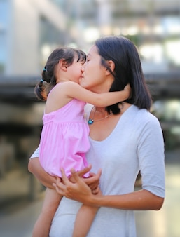 Glückliche liebevolle familie. mutter und kind mädchen küssen und umarmen