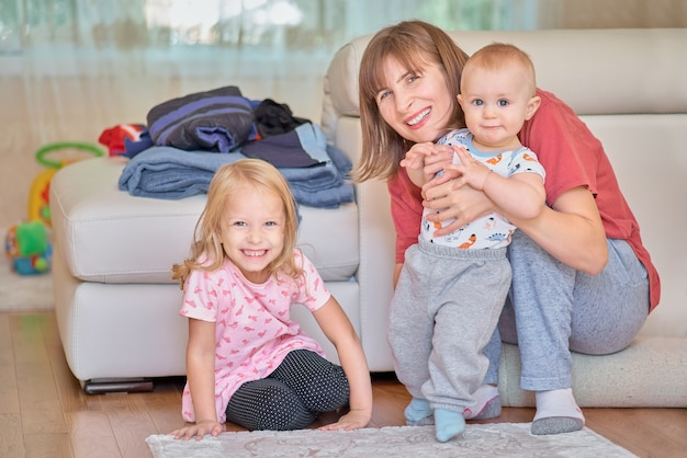 Glückliche liebevolle junge mutter, die ihren kleinen vorschulsohn, nahe bei tochter, lächelnde interessierende mutter der frau nahe bei ihren kindern zu hause sitzen auf dem boden umarmt.