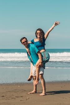 Glückliche liebevolle paare, die spaß auf sandigem strand des sommers haben