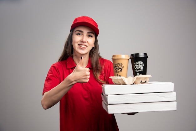 Glückliche lieferfrau, die daumen oben mit pizza und kaffeetassen auf grauer wand macht.