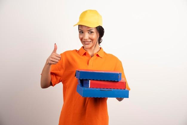 Glückliche lieferfrau, die pizza hält und daumen hoch macht.