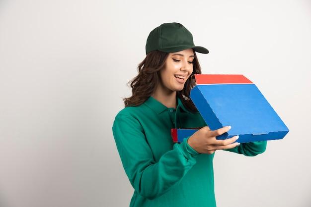 Glückliche lieferfrau, die pizzakasten auf weiß öffnet.