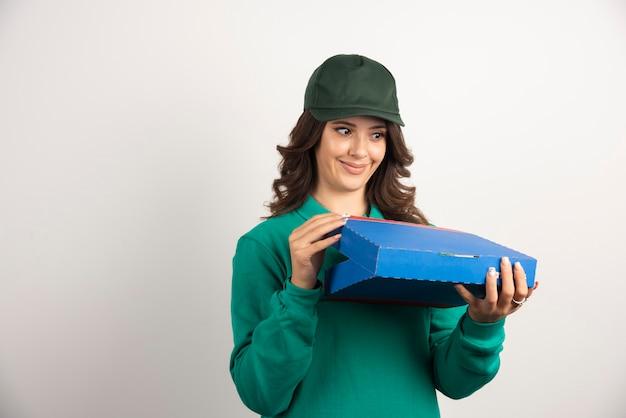 Glückliche lieferfrau, die pizzakasten öffnet.