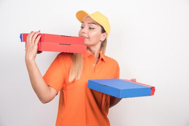 Glückliche lieferfrau, die pizzaschachteln auf weißem hintergrund hält.