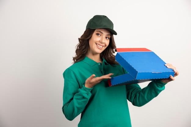 Glückliche lieferfrau in der grünen uniform, die geöffnete pizzaschachtel hält.