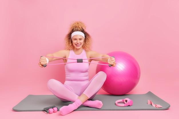 Glückliche lockige junge frau sitzt gekreuzte beine auf fitnessmatte trainiert muskeln