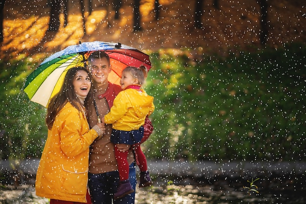 Glückliche lustige familie mit buntem regenschirm unter dem herbstregen.