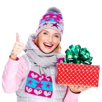 Glückliche lustige frau mit einem geschenk in einer winteroberbekleidung mit daumen hoch zeichen lokalisiert auf weiß