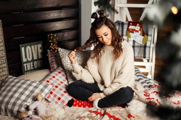 Glückliche lustige junge frau im vintage-strickpullover und in den roten socken auf dem bett am heiligabend