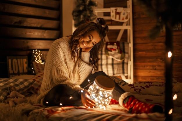 Glückliche lustige junge frau mit einem lächeln im weinlese-strickpullover mit einem magischen glas mit festlichen lichtern auf dem bett