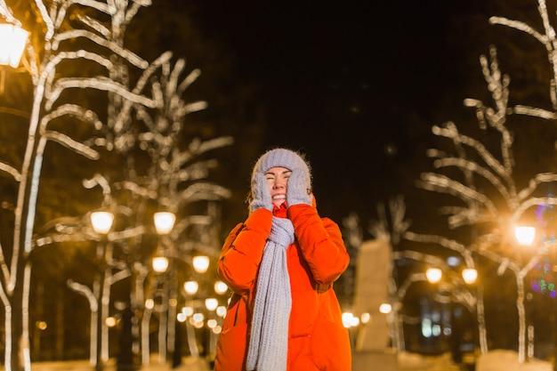 Glückliche lustige junge frau mit winterkleidung hintergrundabendlichterbeleuchtung der stadt. weihnachts- und winterferienkonzept.