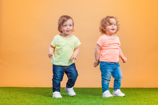 Glückliche lustige mädchen zwillingsschwestern spielen und lachen