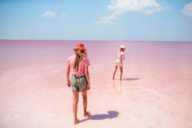 Glückliche mädchen auf einem rosa salzsee an einem sonnigen sommertag.