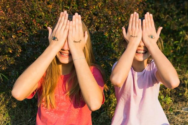 Glückliche mädchen, die an der anlage bedecken ihre augen mit tätowierung an hand stehen