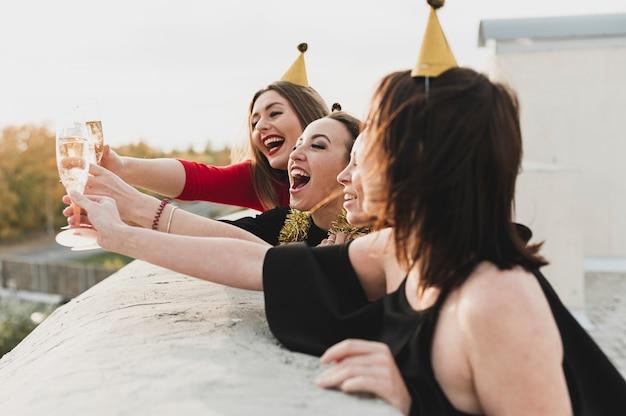 Glückliche mädchen, die auf der dachspitze den sonnenuntergang bewundernd feiern