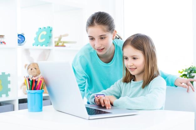 Glückliche mädchen, die im hellen raum am computer arbeiten