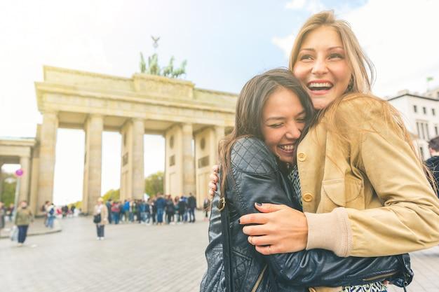 Glückliche mädchen, die sich in berlin treffen und umarmen