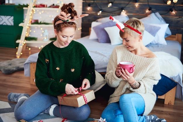 Glückliche mädchen, die weihnachtsgeschenk vorbereiten