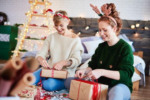 Glückliche mädchen, die weihnachtsgeschenke machen