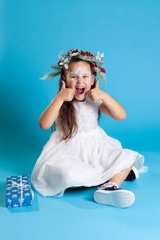Glückliche mädchen in einem weißen weihnachtskleid, das einen kranz und turnschuhe trägt, die auf dem boden sitzen