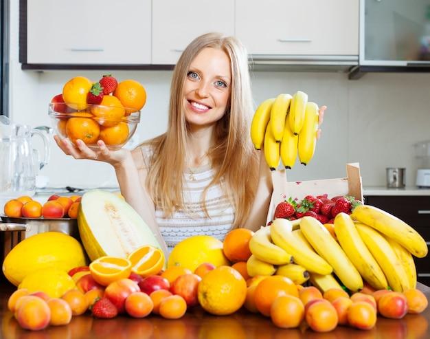 Glückliche mädchen mit verschiedenen früchten in haus küche