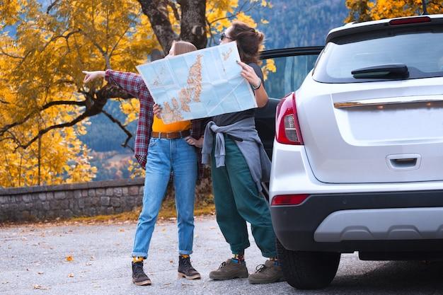 Glückliche mädchen reisen mit dem auto. roadtrip - touristenmädchen mit einer karte stehen in der nähe des autos. österreich