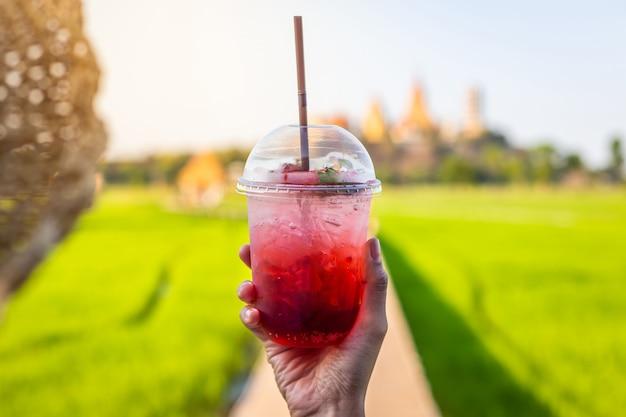 Glückliche mädchenhände, die cocktails oder erdbeersoda in der sommersaison halten